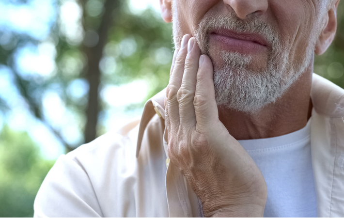 man touching jaw because of tooth pain