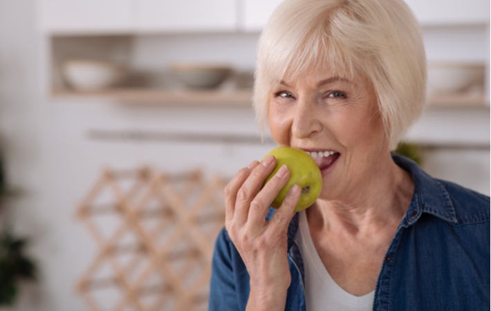older woman smiling and eating a green apple