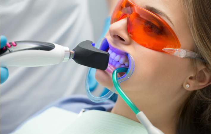 woman getting her teeth whitened at the dentist